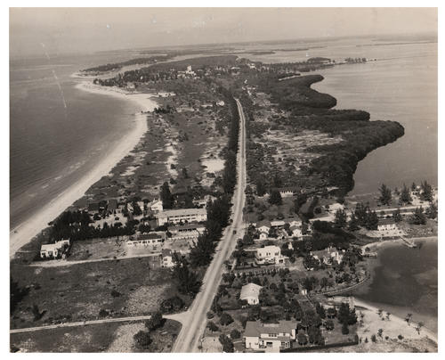 An aerial view photograph taken in 1945 from the North of Bennett Beach. A large main road appears down the middle of the land mass with smaller roads stemming from the main road. Some buildings that appear to be homes and shops are seen below while other areas of land remain undeveloped. White sand beaches and palm trees can be seen along the shores. It's unclear where exactly Bennett Beach is located in Florida and what bodies of water surround the land.