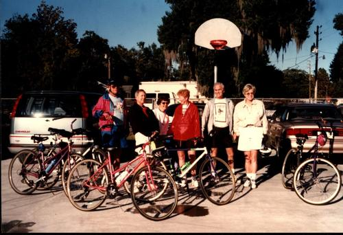 Group photograph of group members about to embark on a bike ride together. Included in the photo from left to right are an unknown gentleman, Jim Erwin, Tootie Erwin, Sylvia Franklin, Marty Franklin, and Joan Vallar.